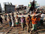 Men with no safety gear carry steel plates cut from broken ships in a ship breaking yard in Chittagong, Bangladesh, on the 12th December 2006.<br /> <br /> Chittagong's ship-breaking yards in Bangladesh are the second largest shipbreaking operation in the world after India. At high tide vessels are driven at full speed up onto one of the world's longest and now most polluted beaches. Here, half of the world's supertankers are hacked and torn apart by an army of workers using blowtorches, sledgehammers and plain brute force. The number of accidents and casualties at the yard is believed to be the highest in the region. Workers cut steel plates continuously without eye protection. Many don't wear uniforms, protective gloves or boots. However, Bangladesh is dependent on shipbreaking for its domestic steel requirements and the industry employs, directly or indirectly, an estimated 100,000 Bangladeshis.<br /> <br /> In recent years shipbreaking has become an issue of major environmental concern. <br /> Shipbreaking yards in developing nations like Bangladesh have lax or no environmental controls, enabling large quantities of highly toxic materials to escape into the environment causing serious health problems among shipbreakers and the local population. Environmental campaign groups such as Greenpeace have made the issue a high priority for their campaigns. <br /> PHOTOGRAPH BY SIMON DE TREY-WHITE<br /> photographer in delhi photographer in delhi