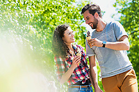 Portrait of young attractive couple walking while eating ice cream