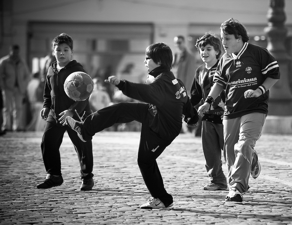 Young boys play football in a piazza. Senigalia, Italy.