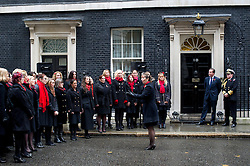 © London News Pictures. 10/11/2012. London, UK. British Prime Minister David Cameron listening to a performance by members of the Military Wives Choir  on Downing Street before members of the Royal Marines from Commando 999 (Royal Marines who serve with the UK emergency services) took part in a  speed march for charity around London to raise funds for wounded service personnel. The event takes place on Remembrance weekend.  Photo credit: Ben Cawthra/LNP