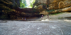 Water trickles over the edge of the rocks of the waterfall in LaSalle Canyon while visitors rest on the sandstone below catching a cool breeze