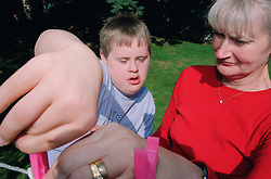 Teenage boy with Downs Syndrome helping mother to hang out washing in back garden,