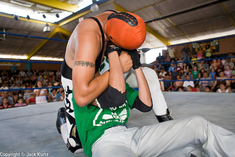 July 13, 2008 -- PHOENIX, AZ: Luchadors (wrestlers) Dr. Parker beats up Fly Boy during a Lucha Libre show at El Gran Mercado in Phoenix. Parker was the rudo (villian) in the bout, Fly Boy the tecnico (good guy). Lucha Libre is Mexican style wrestling. There are heros (Tecnicos) and villians (Rudos). The masks are popular as children's gifts and tourist mementos. As the size of the Mexican community in the Phoenix area has grown, attendance at the Lucha Libre shows has increased. Lucha Libre differs from American style entertainment wrestling in several ways, but principally the wrestlers are more acrobatic and rely less on body slams than American wrestling. The shows, which used to be held only periodically, are now held every week at El Gran Mercado, a flea market and swap meet that caters mostly to the Mexican community in Phoenix.   Photo by Jack Kurtz / ZUMA Press