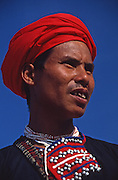 Lao man in traditional headscarf and neck beads with black robe Asia