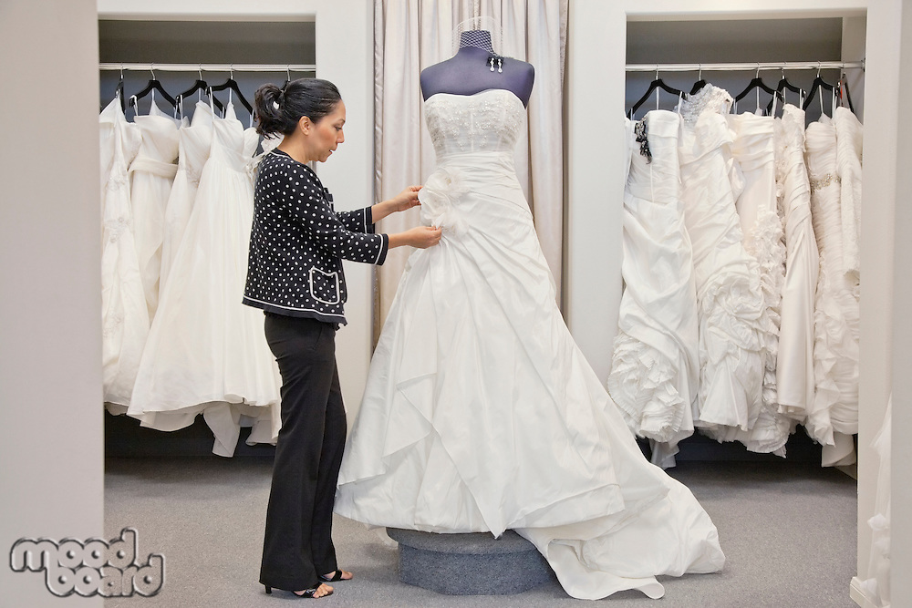 Side view of a mature employee adjusting elegant wedding dress in bridal store