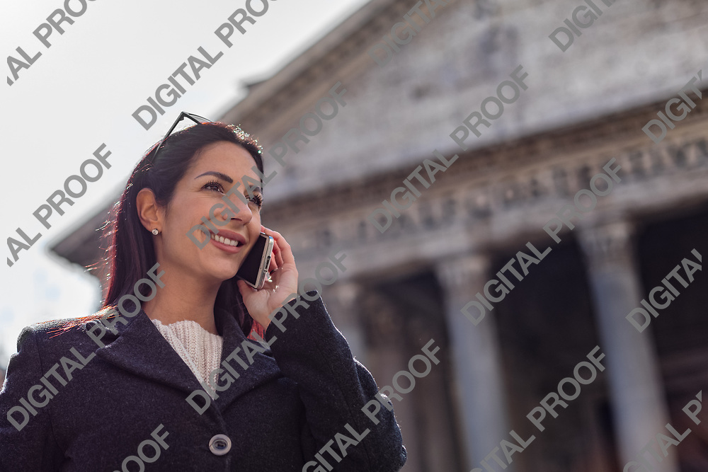 Young charming executive women talks by a mobile phone (cell phone) and smile while visit the Pantheon in Rome, Italy