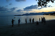 After working at a hotel all day local Thai men play football at sunset on Chawang beach, Koh Samui, Thailand.