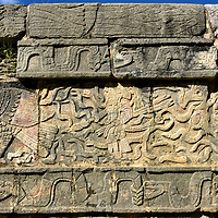 Eagles Holding Heart Carvings along El Tzompantli at Chichen Itza, Mexico <br /> Additional carvings at El Tzompantli depict this Mayan warrior clutching a quiver of arrows and a club tipped with an obsidian (volcanic glass) blade. He is surrounded by images of serpents and flanked by two eagles. Each giant bird is clutching a human heart. Heart extraction was a common form of human sacrifice from 900 &ndash; 1524 AD. The eagle was the ruler of the sky and represented authority, control and wisdom.