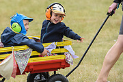 Three boys wearing ear defenders in a trolley being pulled up the hill in the Arena towards the Obelisk Stage - The 2017 Latitude Festival, Henham Park. Suffolk 14 July 2017