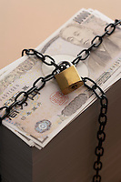 Stack of notes secured by padlock and chain