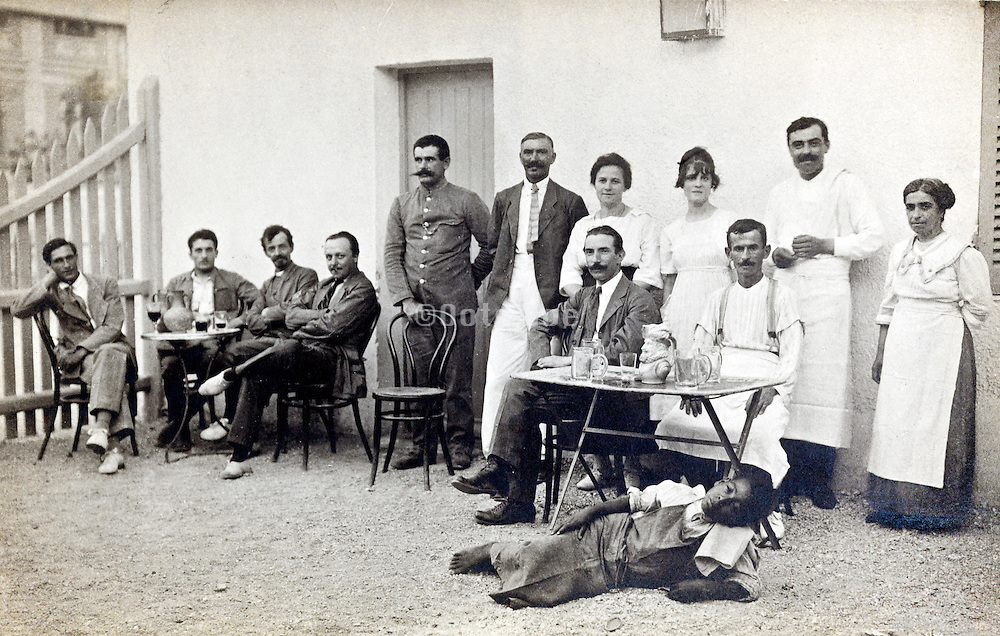 ww1 period soldiers, civilians and workers posing at an restaurant outdoors patio France