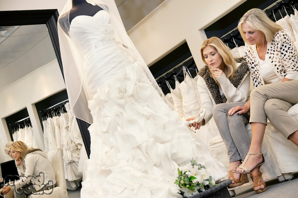Mother and daughter sitting on sofa while looking at elegant wedding dress in bridal store