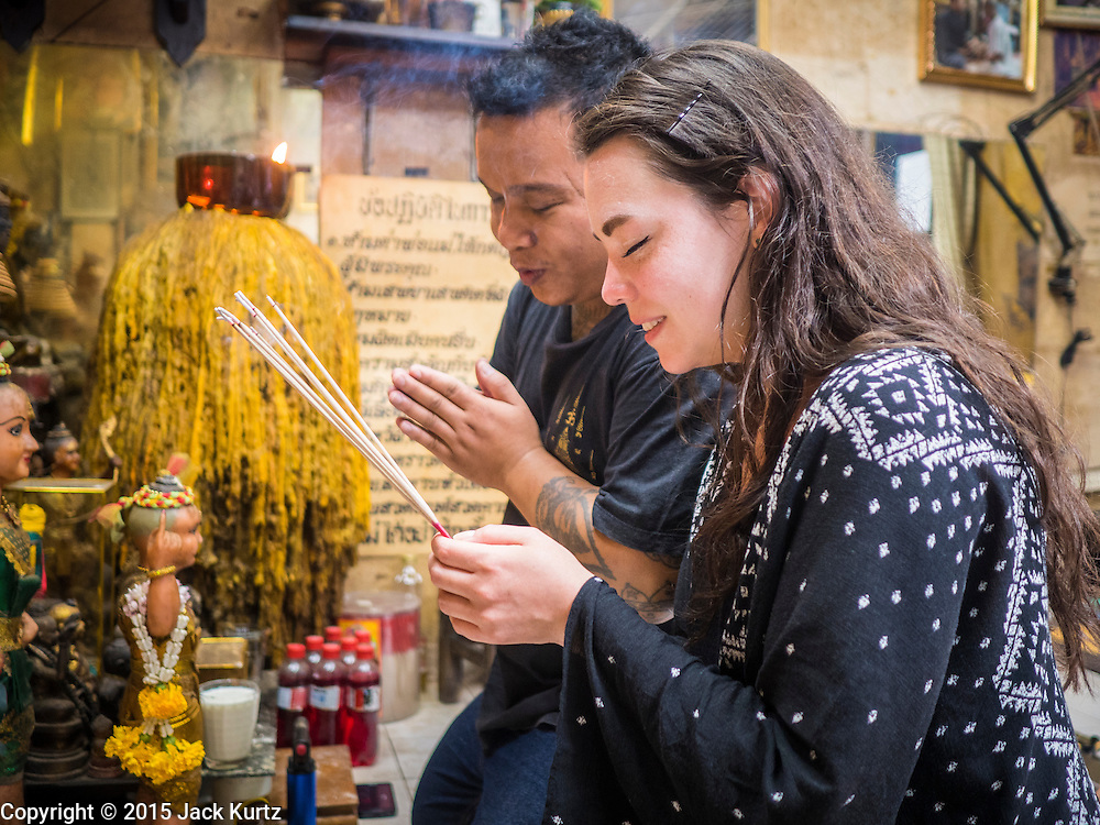 "25 MAY 2015 - BANGKOK, THAILAND: VANESSA, an American visitor to Thailand, prays before getting a Sak Yant tattoo from Ajarn Neng Onnut. Sak Yant (Thai for ""tattoos of mystical drawings"" sak=tattoo, yantra=mystical drawing) tattoos are popular throughout Thailand, Cambodia, Laos and Myanmar. The tattoos are believed to impart magical powers to the people who have them. People get the tattoos to address specific needs. For example, a business person would get a tattoo to make his business successful, and a soldier would get a tattoo to help him in battle. The tattoos are blessed by monks or people who have magical powers. Ajarn Neng, a revered tattoo master in Bangkok, uses stainless steel needles to tattoo, other tattoo masters use bamboo needles. The tattoos are growing in popularity with tourists, but Thai religious leaders try to discourage tattoo masters from giving tourists tattoos for ornamental reasons.       PHOTO BY JACK KURTZ"