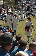 Volunteer actors dressed as French military troops march in front of spectators after re-enacting their surrender to the British during the Fort Michilimackinac Pageant that is part of the Memorial Weekend celebrations in Mackinaw City, Michigan.