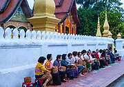Monks and tourists particate in sai bat (morning alms giving), Wat Sesnsoukharam, Sakkaline Road, Luang Prabang, Laos.