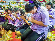20 AUGUST 2015  - BANGKOK, THAILAND: Students from a nearby school pray at the funeral for Yutnarong Singraw Thursday. More than 100 people gathered at Wat Bang Na Nok in Bangkok for the third day of the funeral rites for  Yutnarong Singraw, a Thai man who was killed in the bombing at the Erawan Shrine in Bangkok Monday. Yutnarong was delivering legal documents when the blast occurred. More than 20 people were killed and more than 100 injured in the blast.     PHOTO BY JACK KURTZ