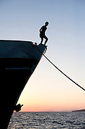 Kids diving off the prow of a ship moored on the island of Silba at sunset, Croatia. © Rudolf Abraham