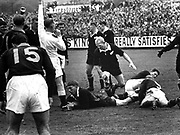 Kel Tremain scores against the Springboks in the first test of the 1965 series at Athletic Park. Ref is Pat Murphy. All Black in support is Red Conway.<br /> Photosport
