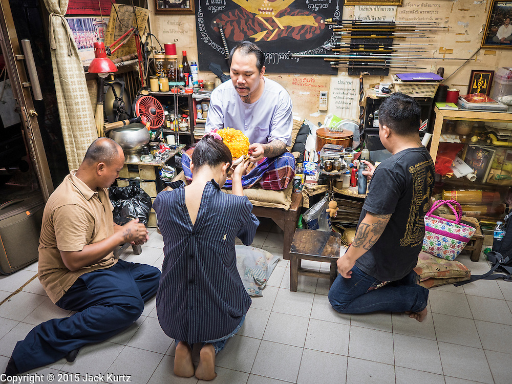 "25 MAY 2015 - BANGKOK, THAILAND:  PAT, a Thai woman getting a tattoo, makes and offering to AJARN NENG ONNUT before Ajarn Neng tattooed her in Sak Yant tattoo parlor. Sak Yant (Thai for ""tattoos of mystical drawings"" sak=tattoo, yantra=mystical drawing) tattoos are popular throughout Thailand, Cambodia, Laos and Myanmar. The tattoos are believed to impart magical powers to the people who have them. People get the tattoos to address specific needs. For example, a business person would get a tattoo to make his business successful, and a soldier would get a tattoo to help him in battle. The tattoos are blessed by monks or people who have magical powers. Ajarn Neng, a revered tattoo master in Bangkok, uses stainless steel needles to tattoo, other tattoo masters use bamboo needles. The tattoos are growing in popularity with tourists, but Thai religious leaders try to discourage tattoo masters from giving tourists tattoos for ornamental reasons.       PHOTO BY JACK KURTZ"