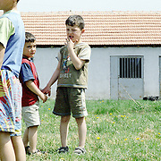 Children in a field outside a school in the outskirts of Pristina, Kosovo.  Schooling is provided with the aid of ngo aid.