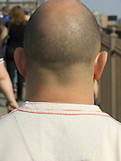 view of the back of balding young man with short shaved hair