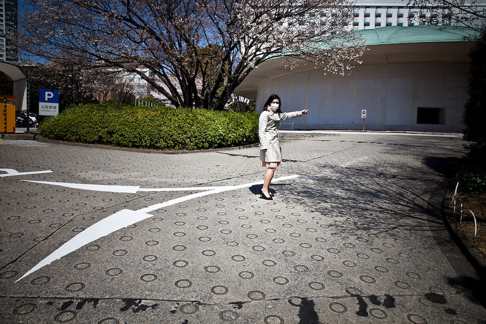 TOKYO, JAPAN, 8 APRIL - Shinagawa - A woman show the way to go when the sign on the floor show the opposite way. April 2012