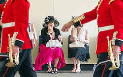 © Licensed to London News Pictures. 17/06/2014. Ascot, UK. A women applies make up whilst a military band passes.  Day one at Royal Ascot 17th June 2014. Royal Ascot has established itself as a national institution and the centrepiece of the British social calendar as well as being a stage for the best racehorses in the world. Photo credit : Stephen Simpson/LNP