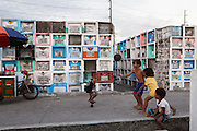 Children who live in a graveyard play and stand on the tombs as a man (left) waits for a candle he lit on a baby's grave to burn down in an inhabited cemetery in Paranaque City, Metro Manila, The Philippines on 18 January 2013. Photo by Suzanne Lee for Save the Children UK