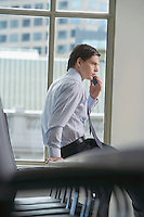 Businessman using mobile phone in office side view