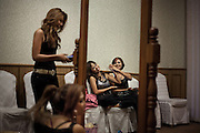 "YANGON,MYANMAR,MARCH 2012: The girls relaxing in the dressing room before a concert.<br /> Burma is a country in Transition. And if that hasn't been made clear enough by the political debates and the recent by-elections, meet the Me N Ma Girls, the first girlband in the country.<br /> The timing couldn't be better. After the April 1st elections in 2012 an always increasing number of investors from all over the world has been visiting Myanmar. After decades of military regime and isolation, the strings of censorship have started loosening up. The government censors in fact for years have banned songs and articles, deleting anything that was seen as ""to provocative"" such as leather outfits and colored wigs.<br /> Describing themselves as Myanmar's first all-girl group, under the management of the Australian dancer and choreographer Nicole May, these five women - coming from either Buddhist or Catholic background and formerly known as Tiger Girls - not only have been challenging censorship laws but they're as well trying to win hearts in a society that in many ways remains man-dominated and socially conservative.<br /> In a country that has been locked up for years, the Me N Ma Girls, embracing western pop culture with skimpy outfits and catchy songs, show with every performance the will of the Burmese youth to come out of a decades-long isolation.<br /> Five girls leading a new form of rebellion: the kind that questions roles and cultural norms."