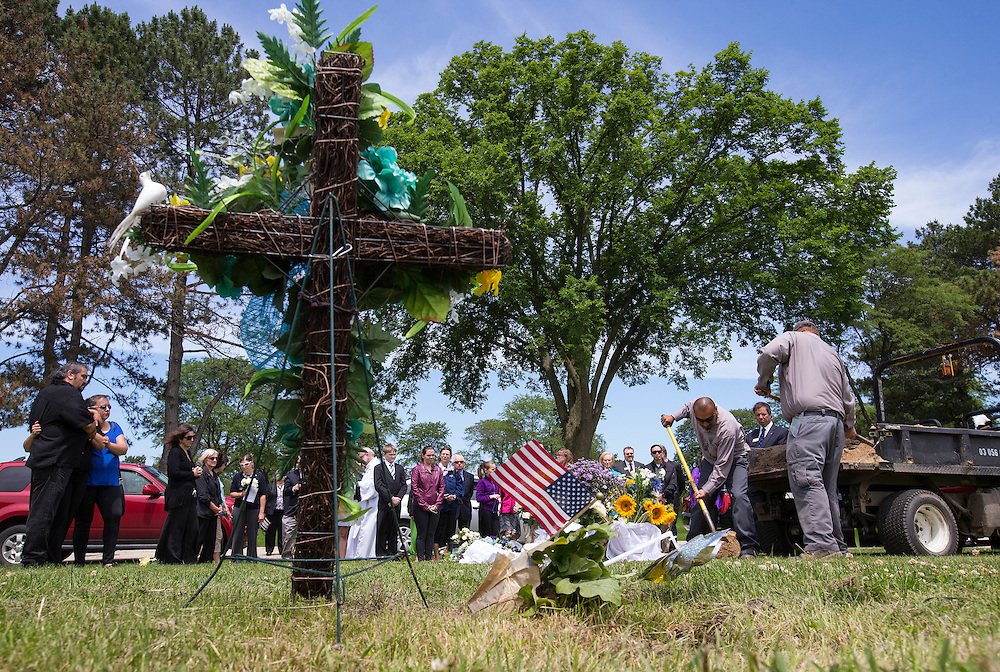 "Workers shovel dirt on to the casket of an abandoned newborn baby boy during a burial service at All Saints Cemetery in Des Plaines, Illinois, United States, June 19, 2015. More than a year after he was found dead in a plastic shopping bag on a Chicago sidewalk, the baby boy was buried by a non-profit group ""Rest in His Arms"" after abandoned by his teenage mother, who is charged with murder.  REUTERS/Jim Young"