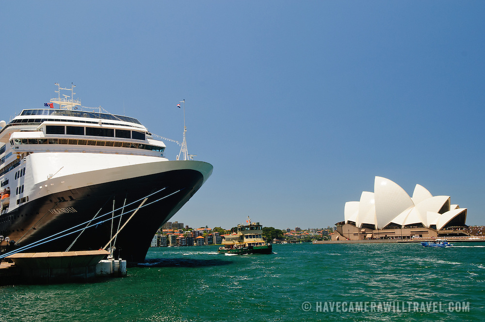 A large cruise ship moored at Circular Quay, next to the Rocks district, with the Sydney Opera House in the background.