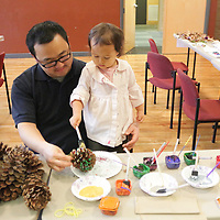 Clara Huang, 3. decorates a Pine Cone Bird Feeder with her father Anthony Huang Saturday December 20, 2014 during Nature Holiday Creations at Halyburton Park in Wilmington, N.C. (Jason A. Frizzelle)