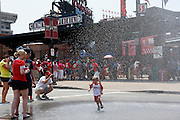 ST. LOUIS, MO - JUNE 30: A young St. Louis Cardinals fan runs through water that was provided by the city fire department outside the stadium before the game against the Pittsburgh Pirates at Busch Stadium on June 30, 2012 in St. Louis, Missouri. The Pirates won 7-3 as temperatures reached 103 degrees during the game. (Photo by Joe Robbins)