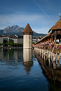 The Chapel Bridge in Lucerne, Switzerland, with Mount Pilatus in the distance.