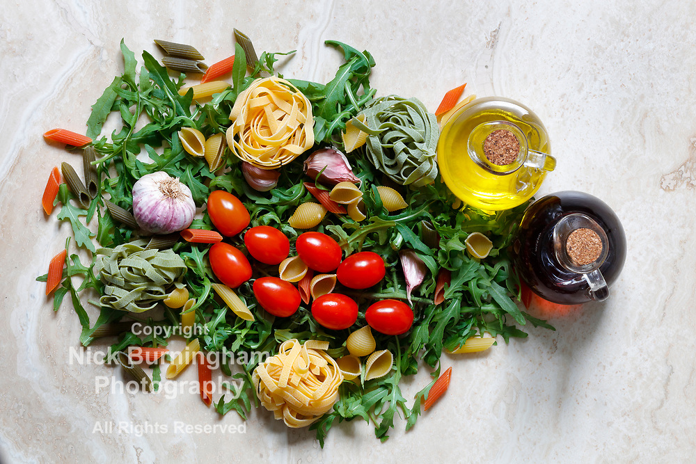 Rocket Arugula with plum tomatoes and garlic with Tagliatelle and penne pasta tricolore ingredients for Italian food on marble table with olive oil