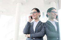 Happy businesswoman using cell phone while leaning on glass wall