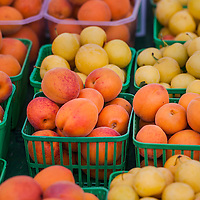 Baskets of apricots and yellow plums at a farmers market