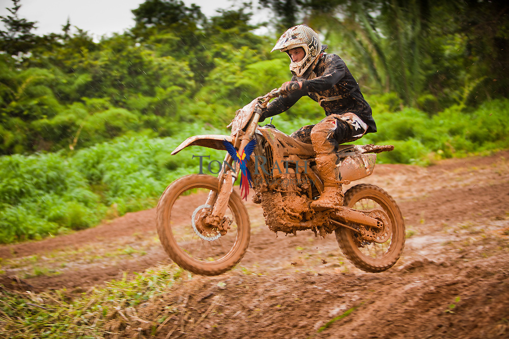 Medium shot shows motocross racer and motorcycle covered in mud initiating a jump on a muddy outdoor trail during extreme sporting event in Belmopan, Belize.