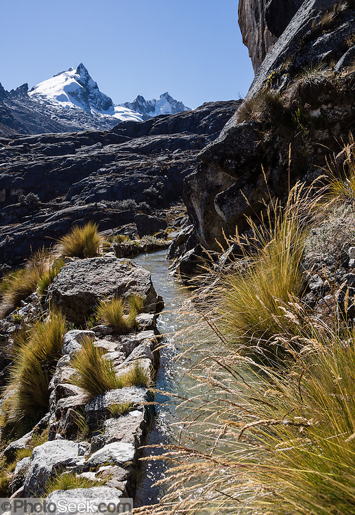 An aquaduct flows from Lake Cullicocha (4628 m or 15,174 ft) below a peak on Nevado Santa Cruz Norte, in the Cordillera Blanca, Andes Mountains, Peru, South America. This was day 9 of 10 days trekking around Alpamayo in Huascaran National Park (UNESCO World Heritage Site).