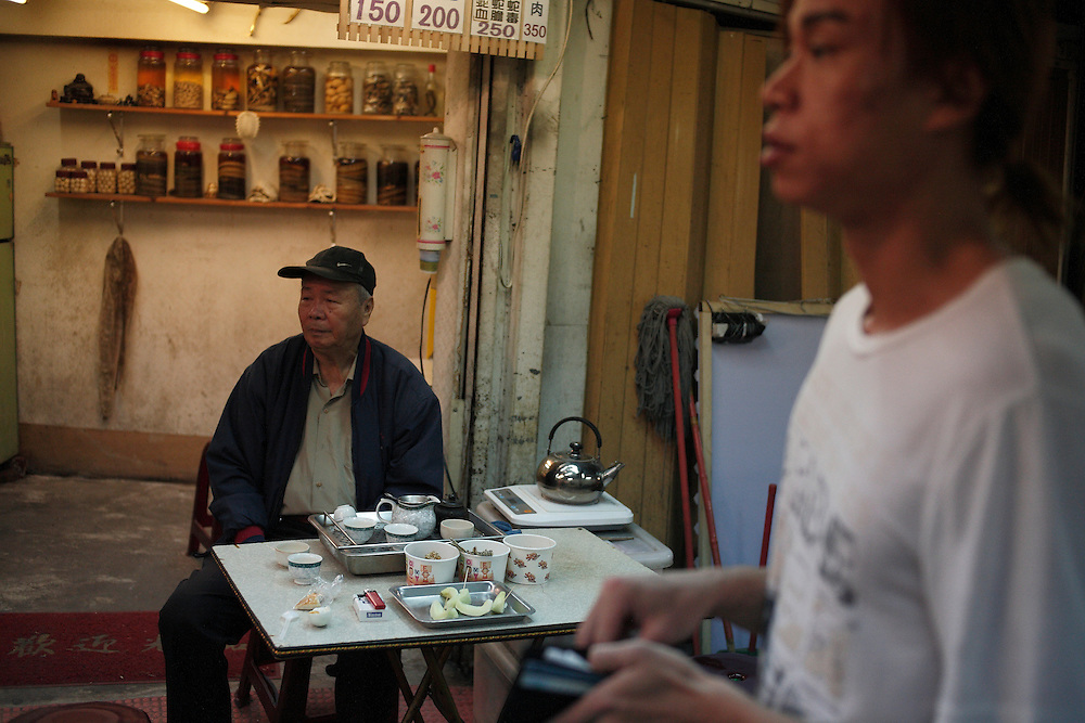 An old man is drinking a snake soup (150 Taiwan dollars = 6 USD)with tea and watermelon , reputed good for health by the chinese medicine, in a night market of Taipeh.