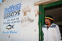 A small-scale subsitence fisher stands outside of his small fish shop, Veldrift, Western Cape, South Africa