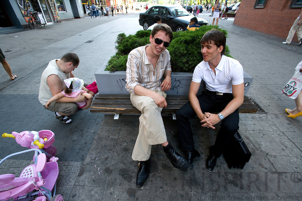 POZNAN - POLAND - 3 JUNE 2008 -- 2 young hope-full men in fashion outfit sitting at a bench in the shopping street. Photo: Erik Luntang/INSPIRIT Photo