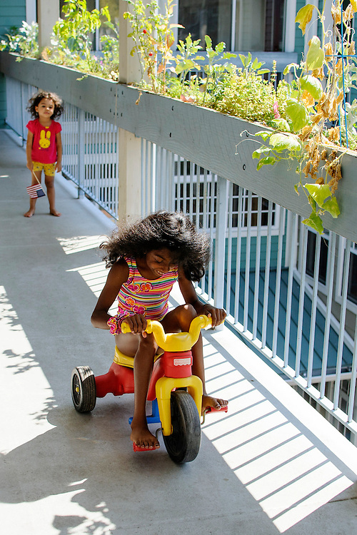 photo by Matt Roth..Sucha Mulholland, 9, foreground, and JoJo Small play on the third floor walkway of the Takoma Village Cohousing complex in Washington, D.C., Saturday, September 22, 2012.