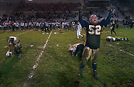 At the end of the San Juaquin Secton title game, a high school football player jubilates to the cheering crowd as the opposition lay dejected in the backround.