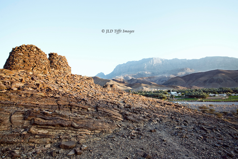 Iron Age beehive tombs aligned along a ridge in the Wadi El Ain, Oman.  Late afternoon sun, clear sky.