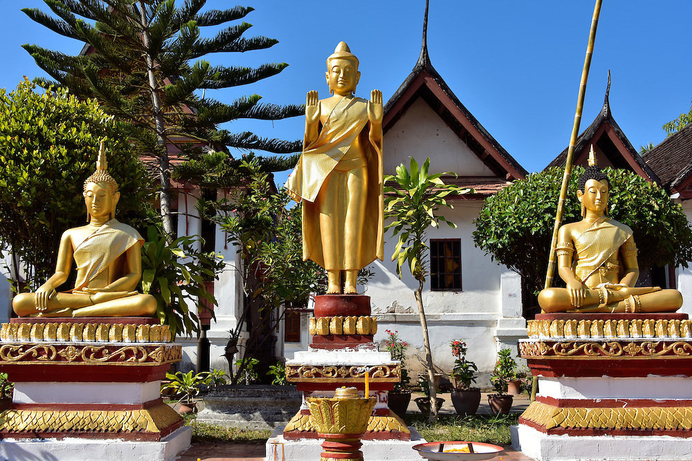 Three Buddha Statues in Courtyard at Wat Mai in Luang Prabang, Laos <br />