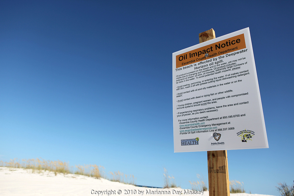 Jul 27, 2010 - Pensacola, Florida, United States - An oil impact notice from the Escambia County Health Department gives warning to tourists of the effects of the Deepwater Horizon oil spill on Pensacola beaches. Waves of gooey tar blobs were washing ashore in growing numbers on the white sand of the Florida Panhandle Tuesday as slicks from the BP spill continue to drift  ashore. The tar balls came ashore after prevailing winds died and were replaced with heavy onshore winds. The tar balls washed up 15 feet at Pensacola Beach, which is already suffering from massive vacation cancellations. BP halted cleanup crews after a tropical storm threat but have reinstated efforts this week..(Credit Image: © Marianna Day Massey/ZUMA Press)