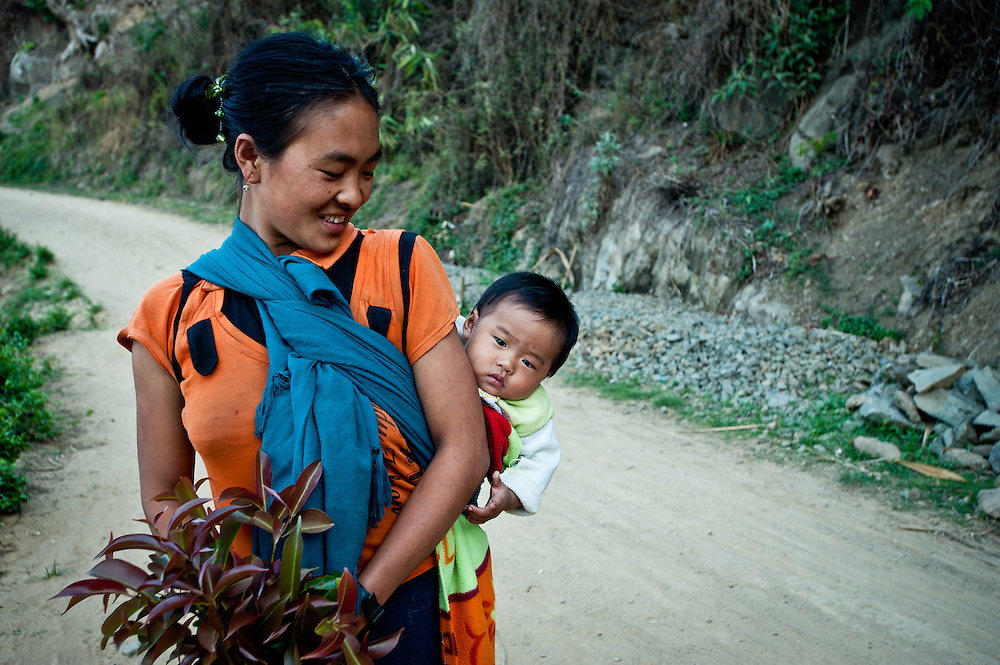 A Naga mother carries her infant on her back as she walks between villages.
