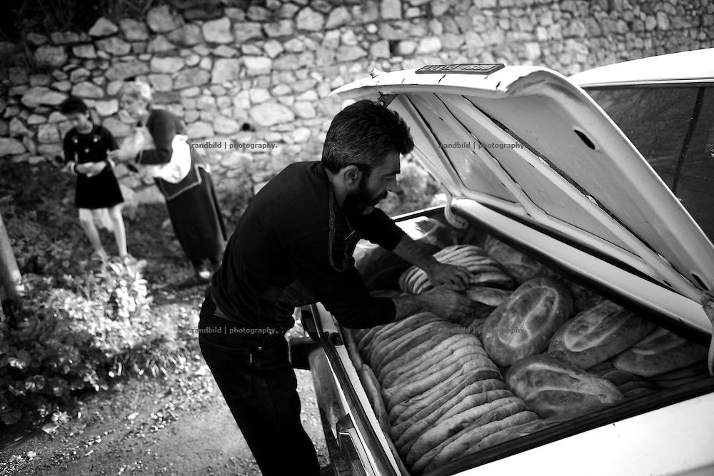 """In the early morning baker Armen load his car and delivers bread to local shops in Shushi. This image is part of the photoproject """"The Twentieth Spring"""", a portrait of caucasian town Shushi 20 years after its so called """"Liberation"""" by armenian fighters. In its more than two centuries old history Shushi was ruled by different powers like armeniens, persians, russian or aseris. In 1991 a fierce battle for Karabakhs independence from Azerbaijan began. During the breakdown of Sowjet Union armenians didn´t want to stay within the Republic of Azerbaijan anymore. 1992 armenians manage to takeover """"ancient armenian Shushi"""" and pushed out remained aseris forces which had operate a rocket base there. Since then Shushi became an """"armenian town"""" again. Today, 20 yeras after statement of Karabakhs independence Shushi tries to find it´s opportunities for it´s future. The less populated town is still affected by devastation and ruins by it´s violent history. Life is mostly a daily struggle for the inhabitants to get expenses covered, caused by a lack of jobs and almost no perspective for a sustainable economic development. Shushi depends on donations by diaspora armenians. On the other hand those donations have made it possible to rebuild a cultural centre, recover new asphalt roads and other infrastructure. 20 years after Shushis fall into armenian hands Babies get born and people won´t never be under aseris rule again. The bloody early 1990´s civil war has moved into the trenches of the frontline 20 kilometer away from Shushi where it stuck since 1994. The karabakh conflict is still not solved and could turn to an open war every day. Nonetheless life goes on on the south caucasian rocky tip above mountainious region of Karabakh where Shushi enthrones ever since centuries."""